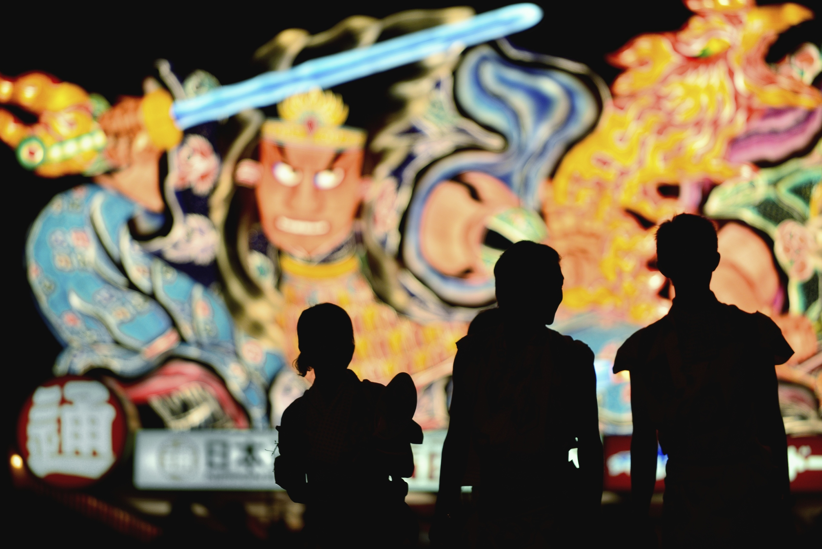 The summer Nebuta festival in Aomori city features giant floats parading through the street at nighttime.