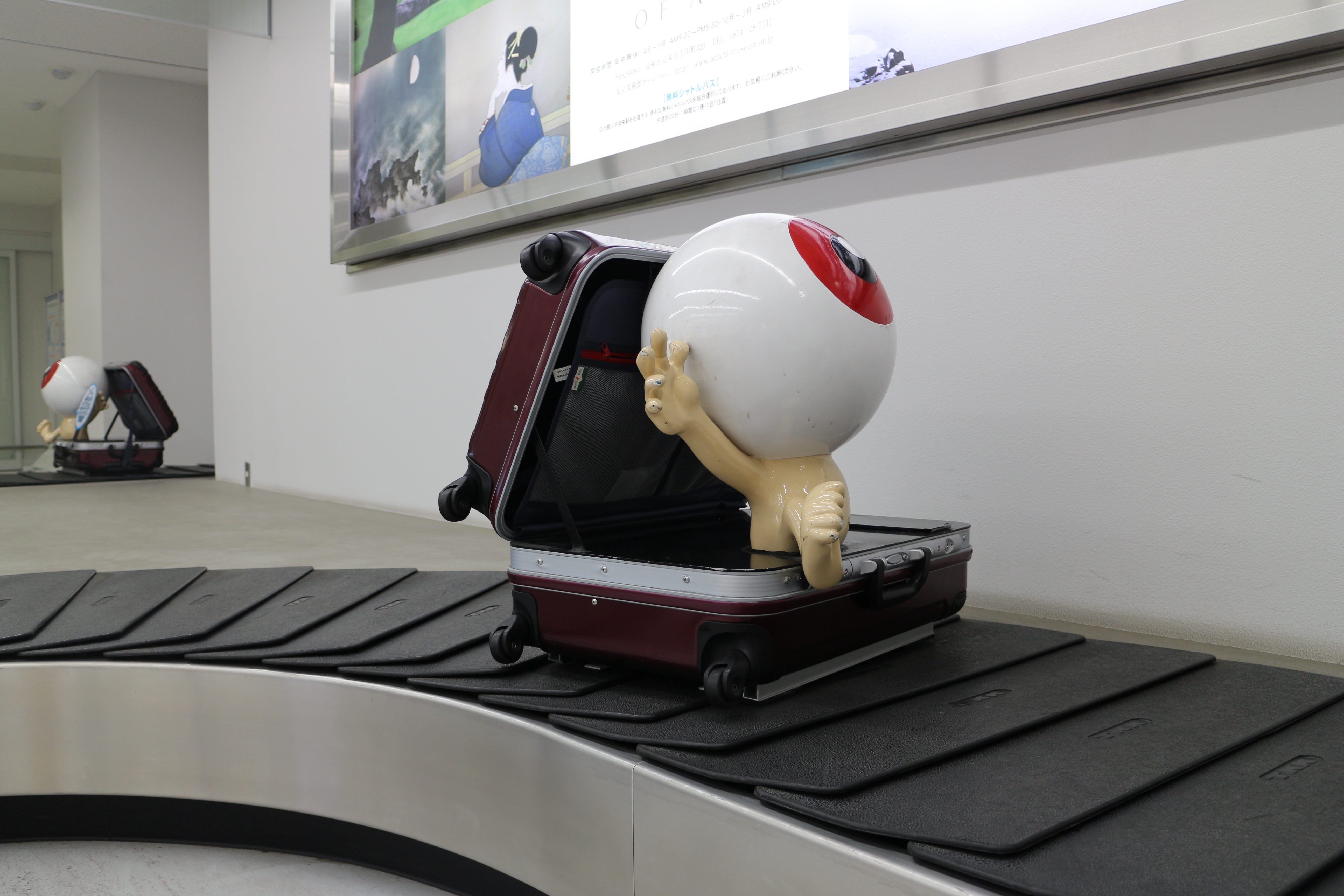 Medama-oyaji statue on luggage carousel at Yonago airport.